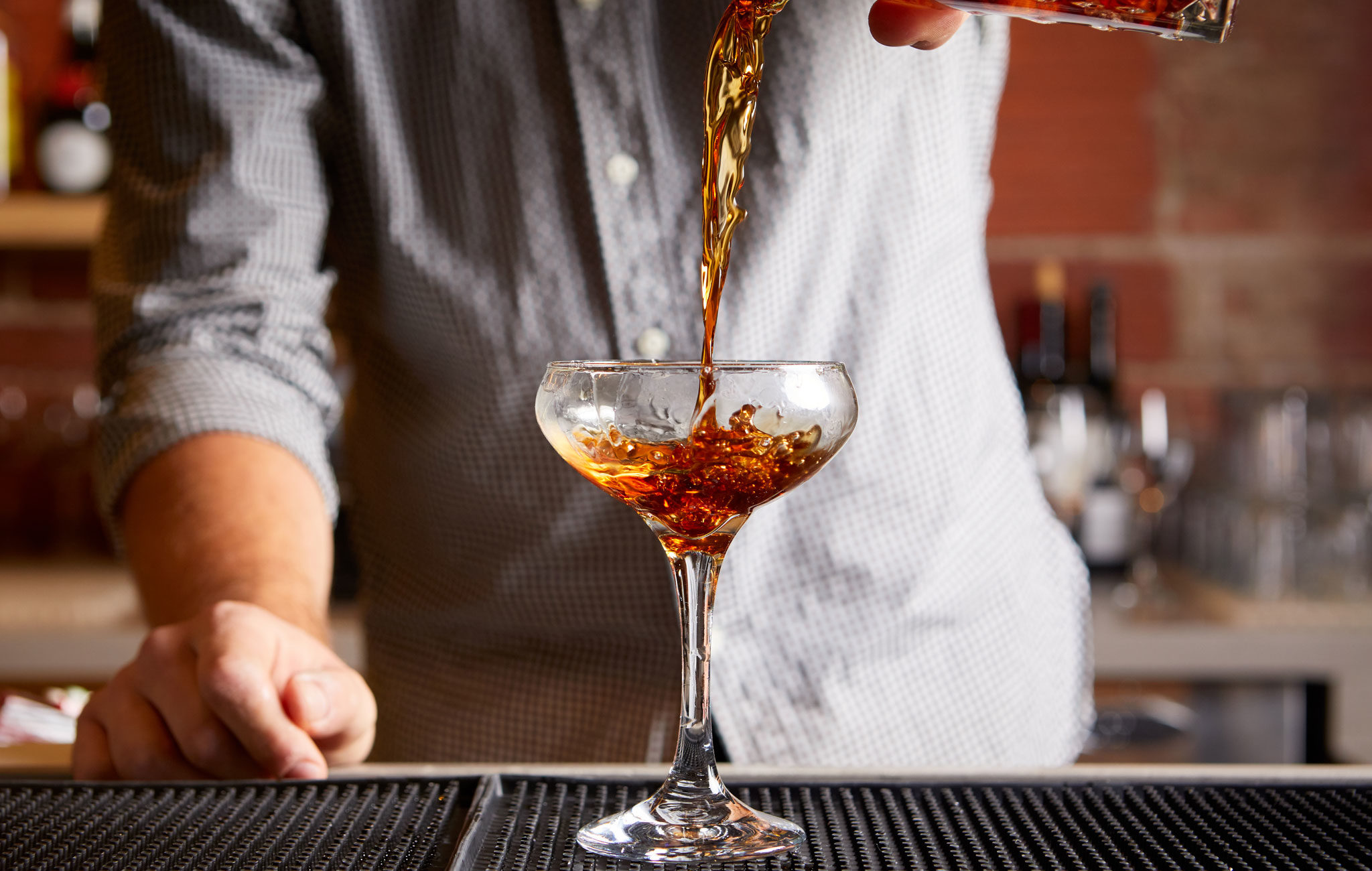 Bartender serving a Rye of the Tiger cocktail
