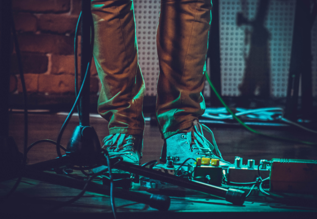 Musician standing in front a pedal board