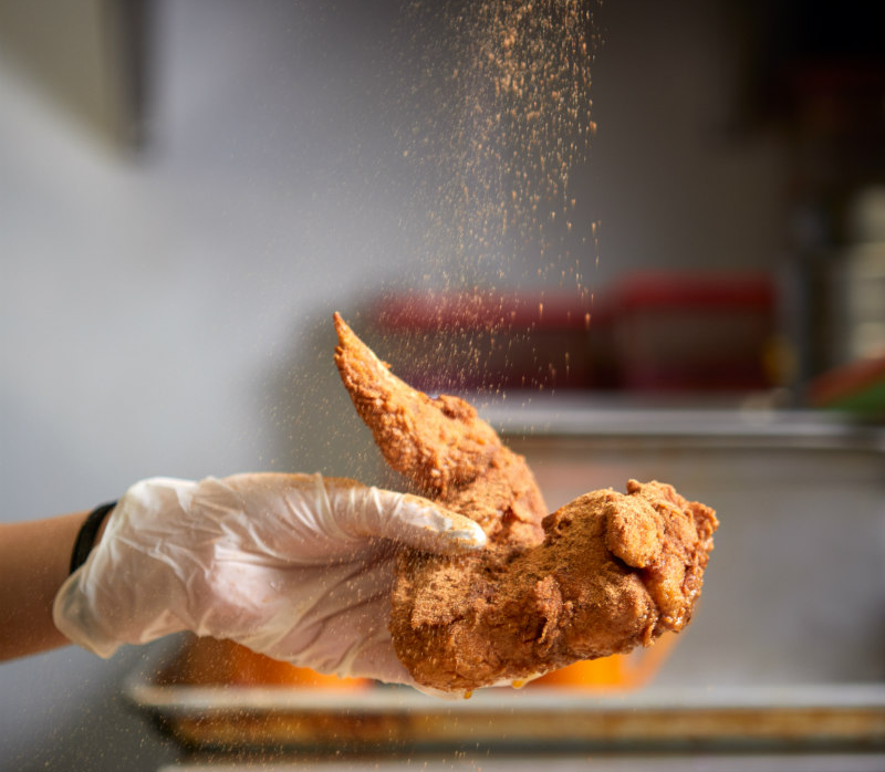Spicing a piece of chicken