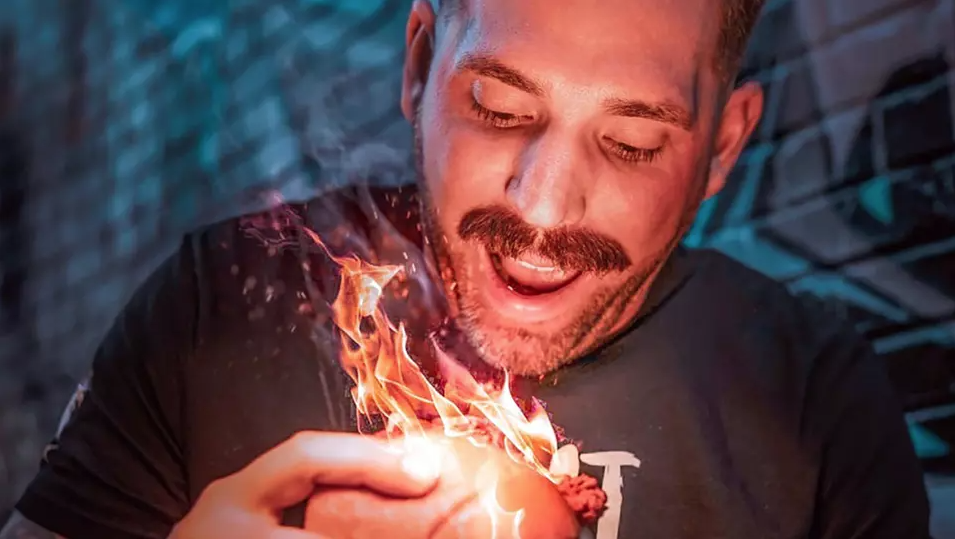 Man about to take a bite of a flaming chicken sandwich